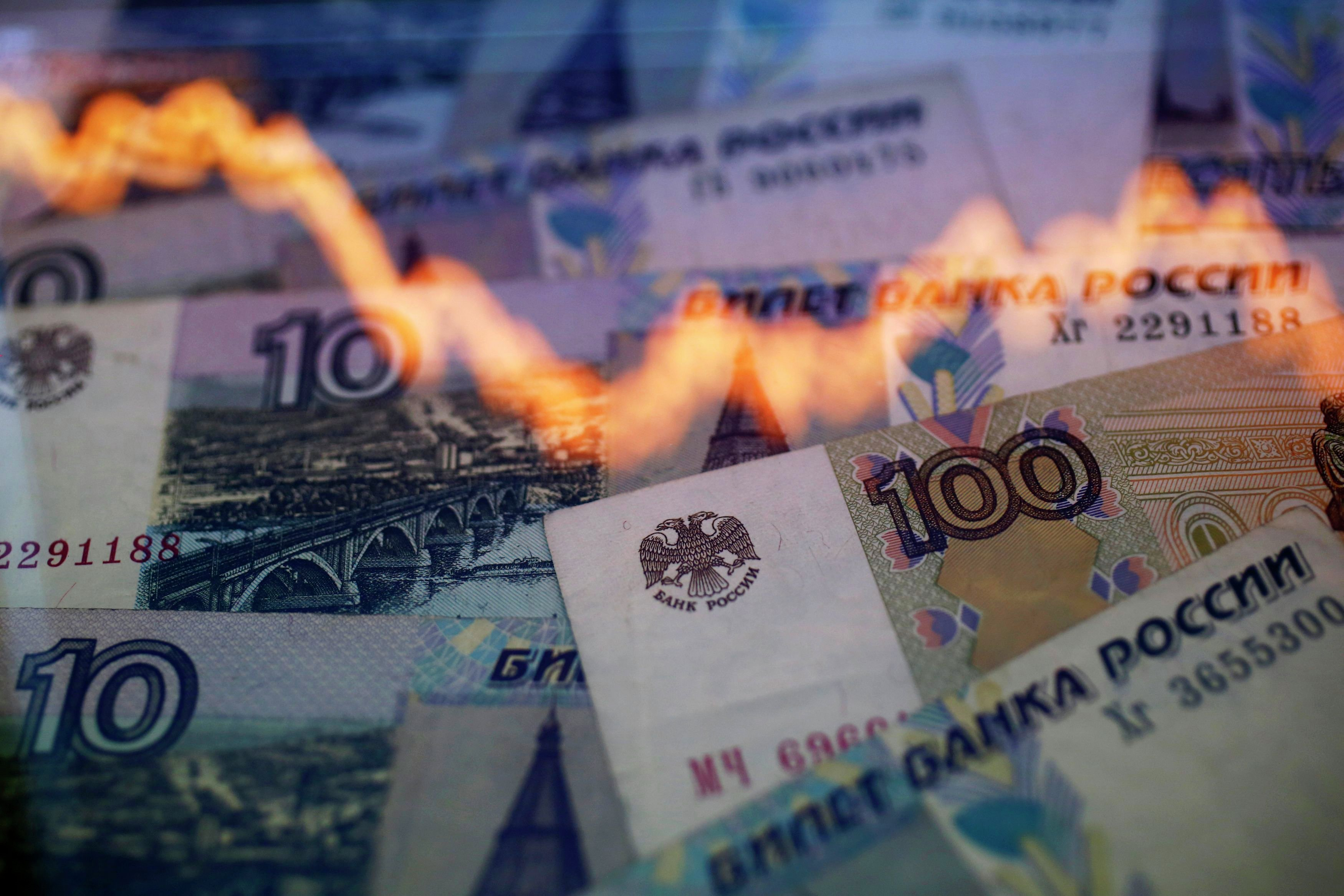 A reflection of a yearly chart of U.S. dollars and Russian roubles are seen on rouble notes in this photo illustration taken in Warsaw November 7, 2014